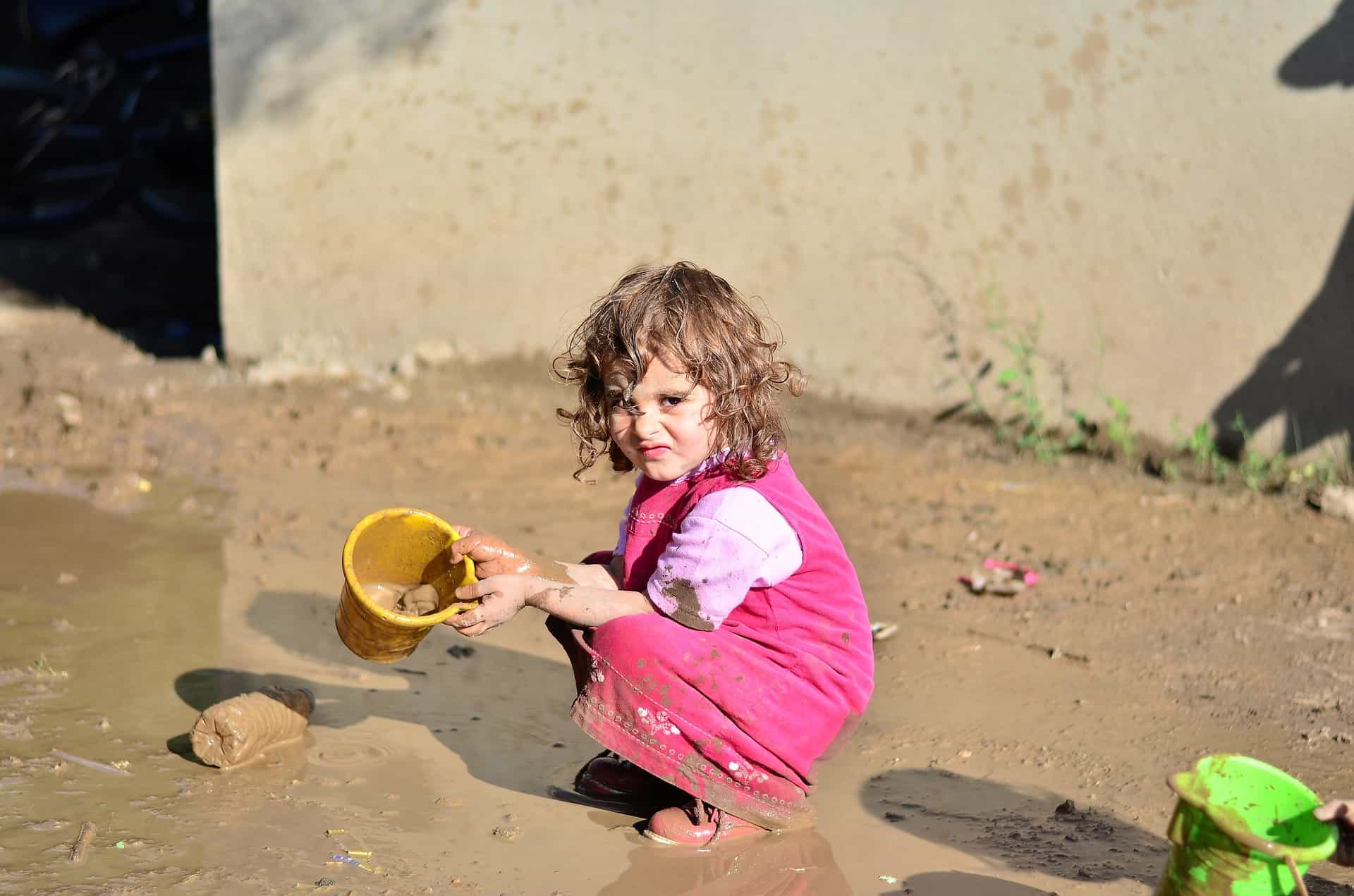 Little girl holding a toy bucket and she is playing at their backyard