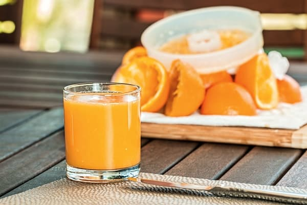 a glass of pure orange juice with its pulp bits