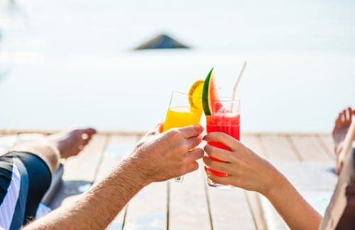 two person toasting drinks